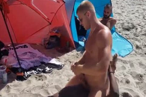 darksome And White homosexual On A Public Beach. Interracial Outdoor